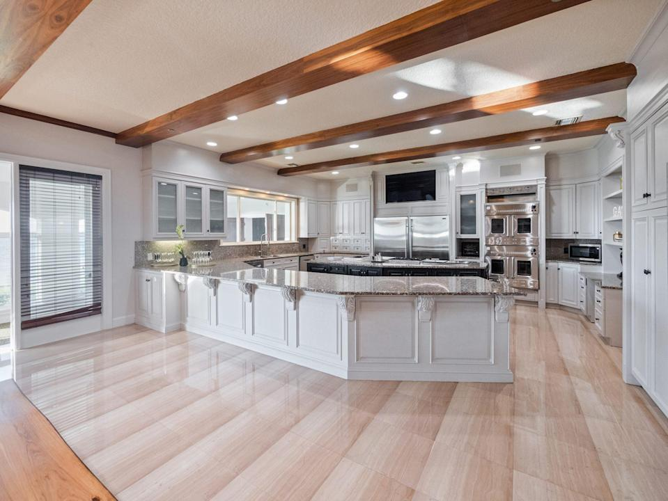 <p>This sleek kitchen has custom wood cabinetry and a six-foot granite-top island.</p>