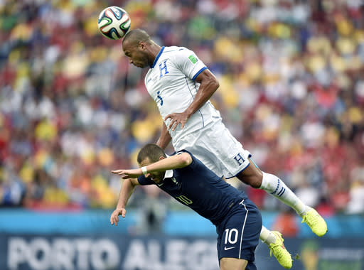 Honduras' Victor Bernardez leaps over France's Karim Benzema to head the ball during the group E World Cup soccer match between France and Honduras at the Estadio Beira-Rio in Porto Alegre, Brazil, Sunday, June 15, 2014. (AP Photo/Martin Meissner)