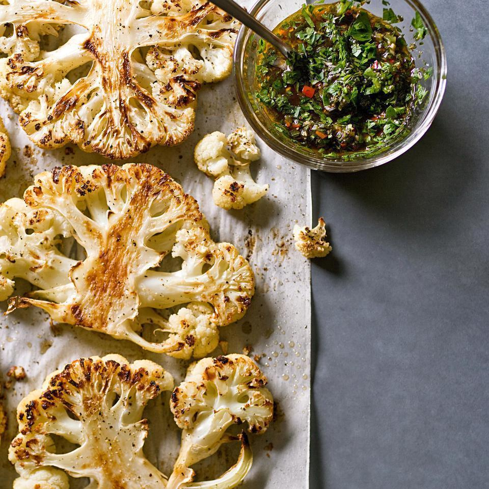 "<p>In this stunning, healthy cauliflower recipe, a head of cauliflower is cut into thick slabs then roasted until caramelized and served with chimichurri, a garlic-herb sauce. The cauliflower steaks make a fine accompaniment to actual steaks, or better still, serve them on their own as a vegetarian alternative to steak. Each head of cauliflower will provide 2 to 3 steaks from the center--the sides tend to crumble. For a truly show-stopping presentation, use the center portion of 2 heads and save the rest of the cauliflower for another recipe that calls for cauliflower florets. <a href=""http://www.eatingwell.com/recipe/252182/cauliflower-steaks-with-chimichurri/"" rel=""nofollow noopener"" target=""_blank"" data-ylk=""slk:View recipe"" class=""link rapid-noclick-resp""> View recipe </a></p>"