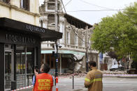 Emergency workers survey damage in Melbourne, Australia, where debris is scattered on a road after part of a wall fell from a building during an earthquake, Wednesday, Sept. 22, 2021. A magnitude 5.8 earthquake caused damage in the city of Melbourne in an unusually powerful temblor for Australia, Geoscience Australia said. (James Ross/AAP Image via AP)