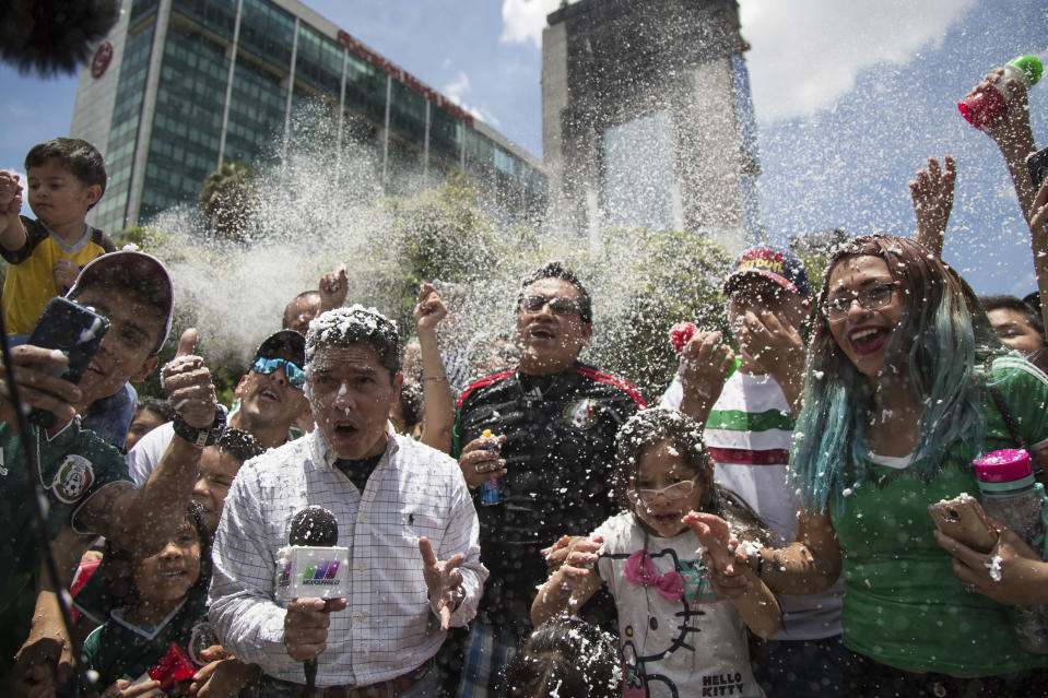 World Cup shock: Mexico TV reporters get in amongst the action in Zocalo Square after the country's surprise win over Germany. (PA)