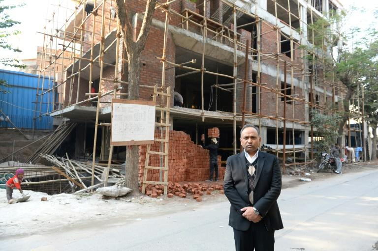 Indian lawyer Naresh Gupta poses outside an under-construction building in New Delhi