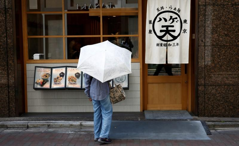 FILE PHOTO: A woman holding a parasol looks at a menu board in front of a restaurant at a shopping district in Tokyo