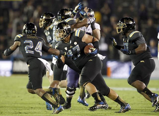 UCLA defensive end Eddie Vanderdoes, center, runs with the ball behind cornerback Ishmael Adams (24) after he recovered a Washington fumble in the first quarter of an NCAA college football game, Friday, Nov. 15, 2013, in Pasadena, Calif. (AP Photo/Alex Gallardo)