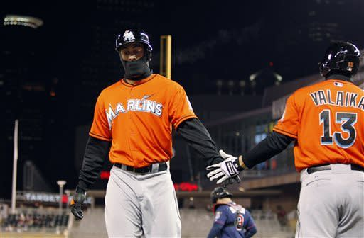 Miami Marlins' Giancarlo Stanton, left, is congratulated by Chris Valaika (13) after scoring on Rob Brantly's RBI double against Minnesota Twins starting pitcher Mike Pelfrey during the fifth inning in the second baseball game of a doubleheader Tuesday, April 23, 2013, in Minneapolis. (AP Photo/Genevieve Ross)