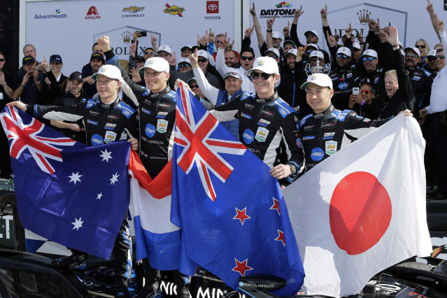 From left to right, Konica Minolta Cadillac DPi-V.R drivers Ryan Briscoe, Renger van der Zande, Scott Dixon and Kamui Kobayashi celebrate with their national flags in Victory Lane after winning the Rolex 24-hour auto race at Daytona International Speedway, Sunday, Jan. 26, 2020, in Daytona Beach, Fla. (AP Photo/Terry Renna)