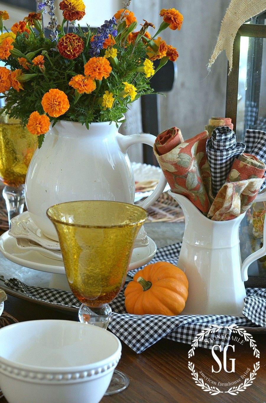 "<p>Here's proof that sometimes practical is best: Roll up cloth napkins and tuck them into a pitcher for an inevitable spill. To brighten up the spread, stick cheery mums in a matching jug.</p><p><em><a href=""http://www.stonegableblog.com/fall-home-tour/"" rel=""nofollow noopener"" target=""_blank"" data-ylk=""slk:Get the tutorial at Stone Gable »"" class=""link rapid-noclick-resp"">Get the tutorial at Stone Gable »</a></em></p>"