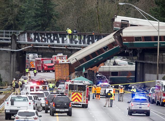 <p>DEC. 18, 2017 – Emergency crews work at the scene of a Amtrak train derailment in DuPont, Washington. At least three people were killed when a passenger train car plunged from the bridge. The derailment also closed southbound I-5. (Photo: Stephen Brashear/Getty Images) </p>