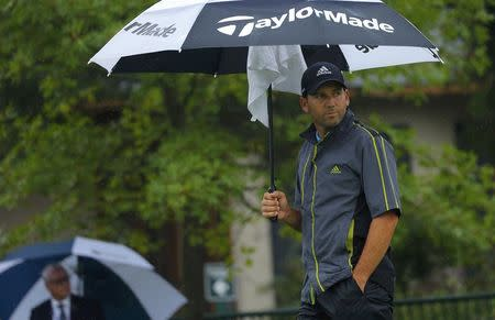 Sergio Garcia of Spain looks from under an umbrella during a rain delay prior to the start of the second round of the 2014 PGA Championship at Valhalla Golf Club in Louisville
