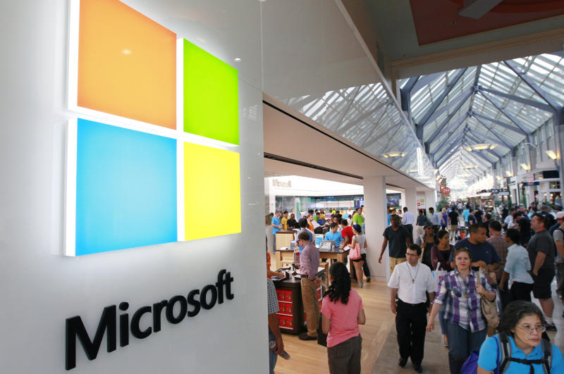 A new Microsoft Corp. logo, left, is seen on an exterior wall of a new Microsoft store inside the Prudential Center mall, in Boston, Thursday, Aug. 23, 2012. The introduction of the new logo marks the first time that Microsoft Corp has revamped its logo in 25 years. (AP Photo/Steven Senne)