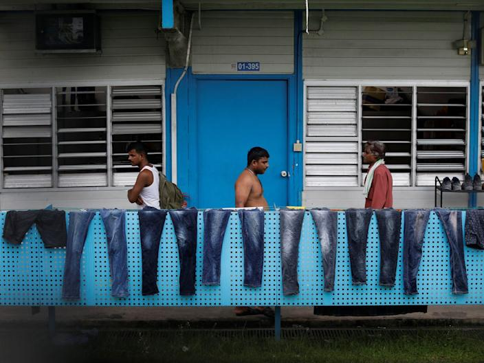 <br>Workers pass a row of pairs of jeans hung to dry at Punggol S11 workers' dormitory in Singapore on April 6, 2020.
