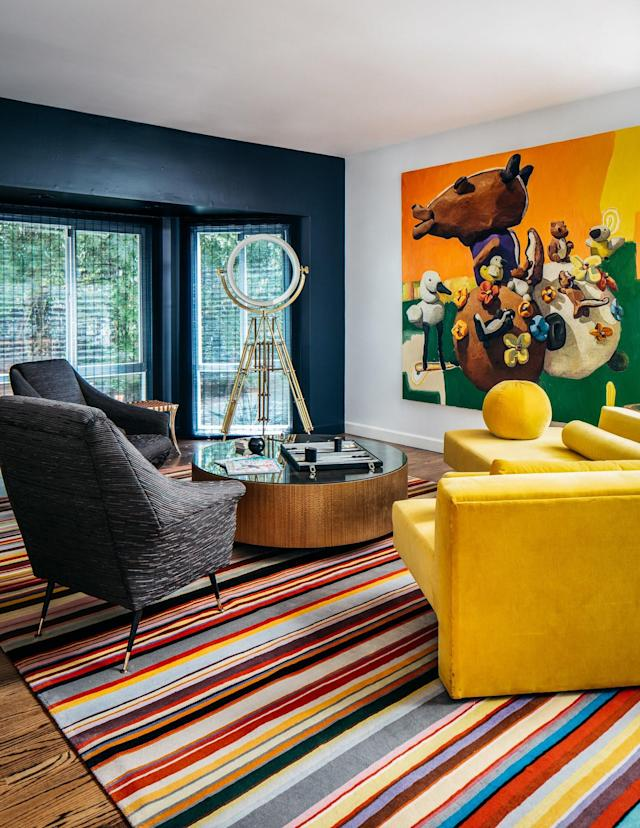 """This house inspired me to think of 1930s Screwball Romanic Comedies,"" said Stallings. Nothing short of Technicolor, the space is alive with vibrancy. It's hard to imagine, but the Paul Smith rug from the Rug Company actually anchors the space. A playful oil painting by Peter Opheim is the room's crown jewel, resting above furnishings from Coup d'Etat."