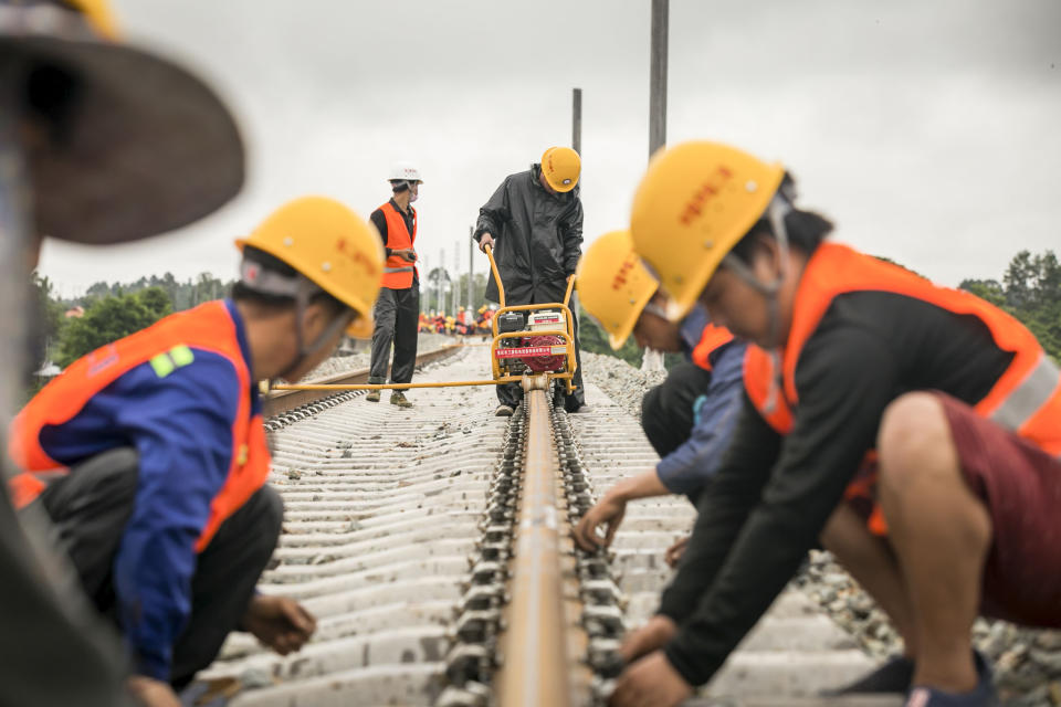 VIENTIANE, June 18, 2020 -- Workers from China Railway No.2 Engineering Group screw the welded seamless rails of the China-Laos railway in the northern suburb of Vientiane, Laos, on June 18, 2020.   The CREC-2 has welded the first seamless rails for the China-Laos railway in the northern suburb of Lao capital Vientiane on Thursday morning.     The seamless rail, also known as continuous welded rail which eliminates rail joints, can improve the duration of steel rails, reduce the maintenance costs of locomotives and tracks, improve the stability and speed of trains, and enhance travel comfort.     The China-Laos Railway is a project of the China-proposed Belt and Road Initiative, with a joint effort, aiming to convert Laos from a landlocked country to a land-linked hub.     The project started in December 2016 and is scheduled to be completed and open to traffic in December 2021. (Photo by Kaikeo Saiyasane/Xinhua via Getty) (Xinhua/ via Getty Images)