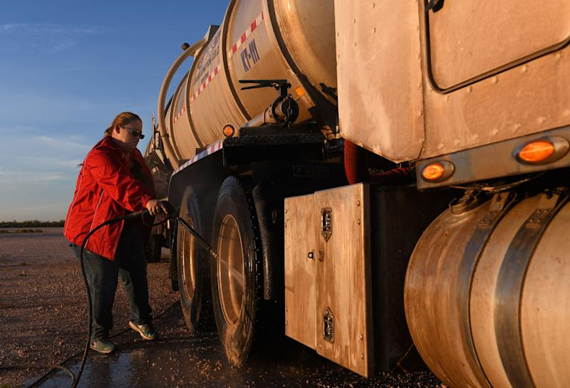 Tara Smith washes an oil tank truck in a yard west of Odessa.