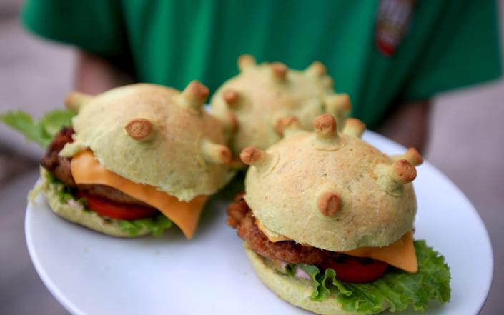 A man holds up coronavirus-themed burgers at a pizza restaurant in Hanoi, Vietnam - SHUTTERSTOCK