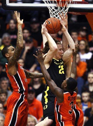 Oregon forward E.J. Singler (25) goes to the basket as Oregon State's Eric Moreland, left, and Ahmad Starks (3) defend in the first half of an NCAA college basketball game, Sunday, Feb. 26, 2012, in Corvallis, Ore. (AP Photo/Rick Bowmer)