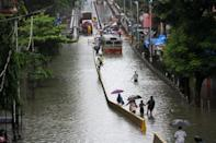 MUMBAI, INDIA - AUGUST 4: People make their way through a flooded road due to heavy monsoon rain in Mumbai, India on August 4, 2020. (Photo by Imtiyaz Shaikh/Anadolu Agency via Getty Images)