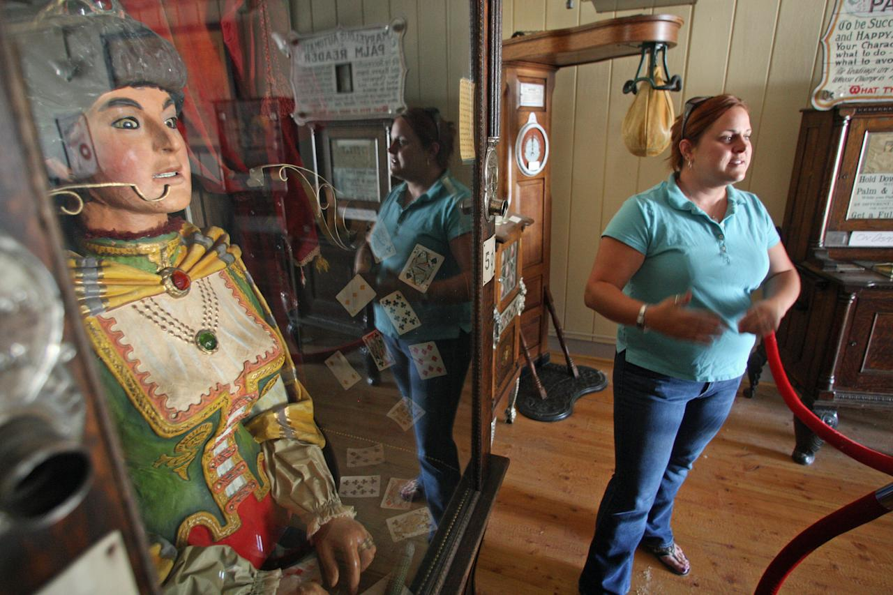 In this July 28, 2011 photo, Janna Norby, curator of collections for the Montana Heritage Commission, stands near an antique Gypsy fortune teller machine, that sat for decades in this Virginia City, Mont., restaurant and has received a multimillion dollar offers from curators including magician David Copperfield. Collectors say the 100-year-old machine that speaks your fortune may be the last of its kind. (AP Photo/Michael Albans)