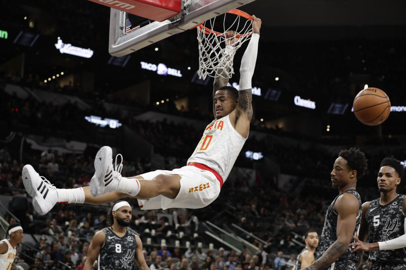 Atlanta Hawks forward John Collins (20) scores over San Antonio Spurs guard DeMar DeRozan, second from right, during the first half of an NBA basketball game in San Antonio, Friday, Jan. 17, 2020. (AP Photo/Eric Gay)