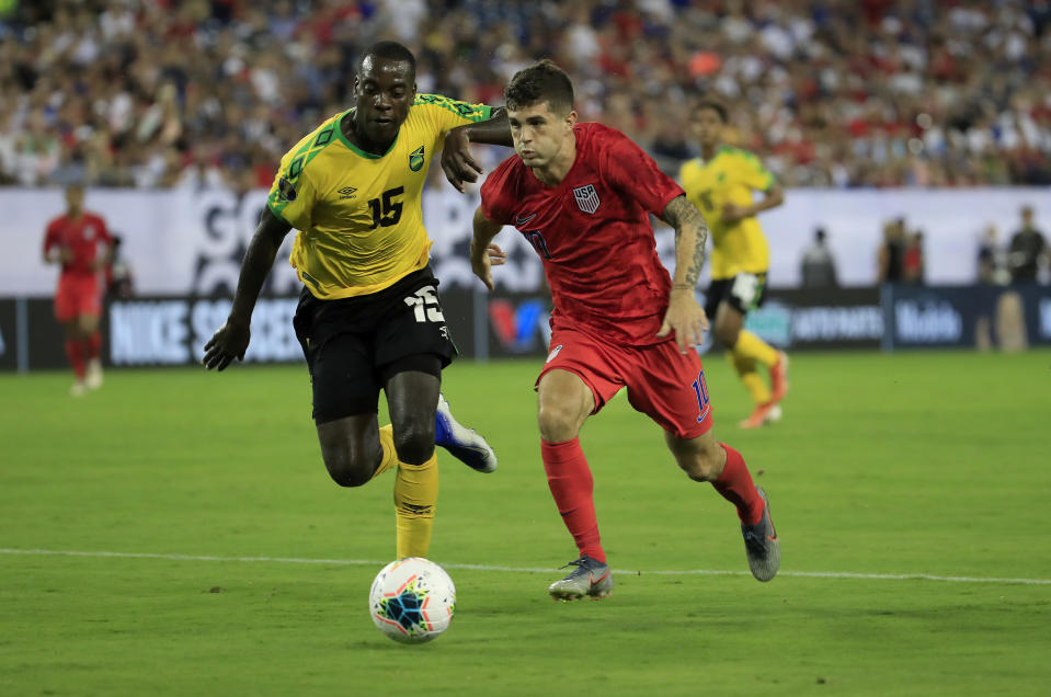 NASHVILLE, TENNESSEE - JULY 03:  Christian Pulisic #10 of United States and Je-vaughn Watson #15 of Jamaica compete for the ball in the semifinal game of the 2019 CONCACAF Gold Cup at Nissan Stadium on July 03, 2019 in Nashville, Tennessee. (Photo by Andy Lyons/Getty Images)