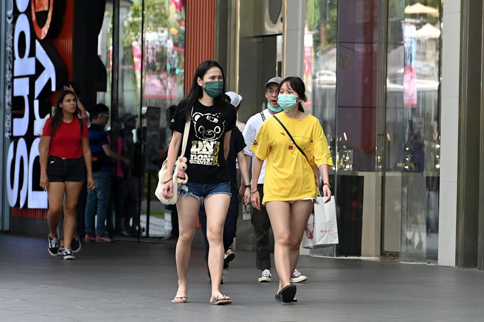 People wearing surgical masks amid fears about the spread of the COVID-19 coronavirus walk past a shopping mall in Singapore on 26 February. (Photo: AFP)