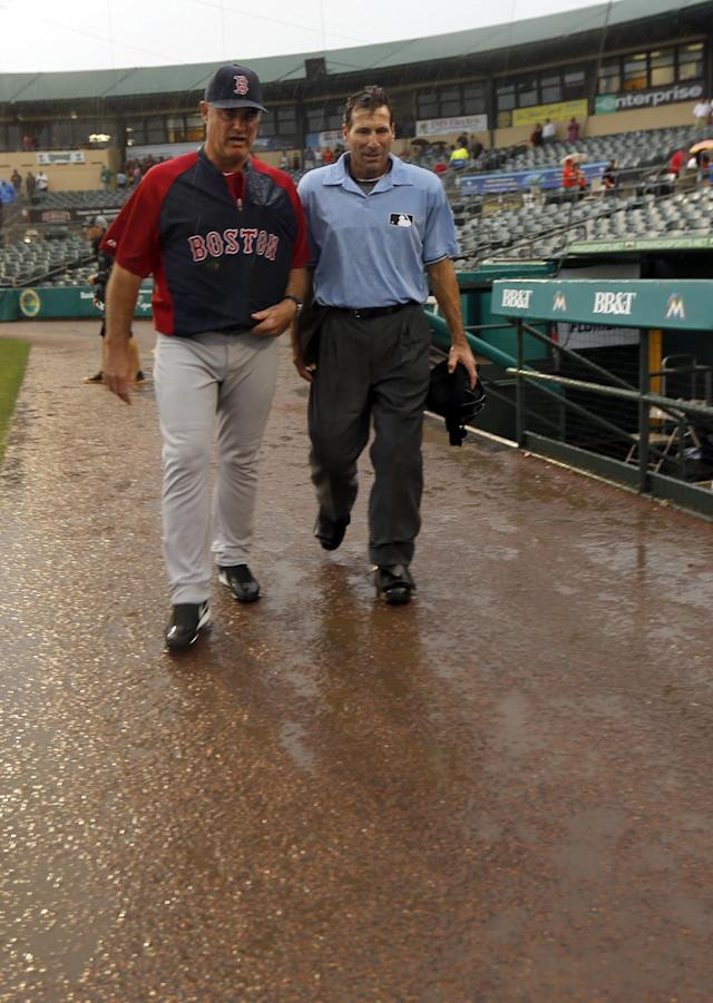 Boston Red Sox manager John Farrell, left, and umpire Angel Hernandez leave the field after a rain delay was called during the eighth inning of an exhibition spring training baseball game between the Miami Marlins and the Boston Red Sox Thursday, March 6, 2014, in Jupiter, Fla. (AP Photo/Jeff Roberson)