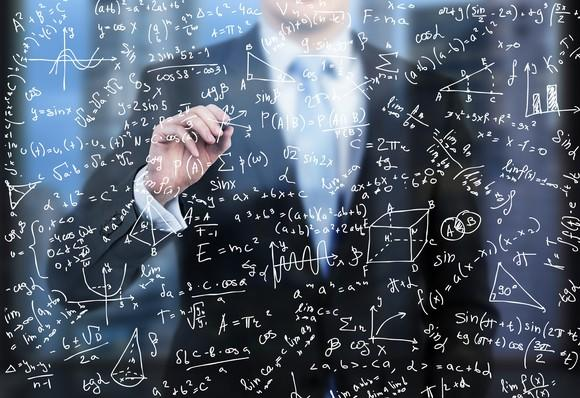 A man in a suit writes formulas on a glass wall in front of him.