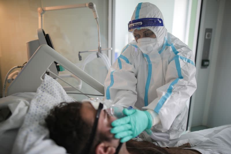 A nurse adjusts the mask that helps Raul Adin, 20, breathe, in the ICU unit for COVID-19 patients at Marius Nasta Institute of Pneumology, in Bucharest