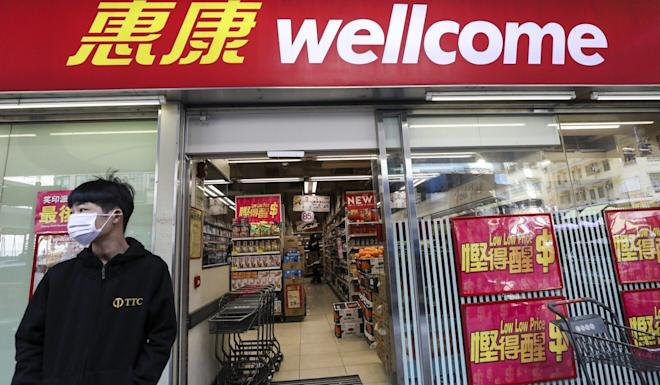 A man stands in front of a Wellcome supermarket on Mong Kok Road. Photo: Nora Tam