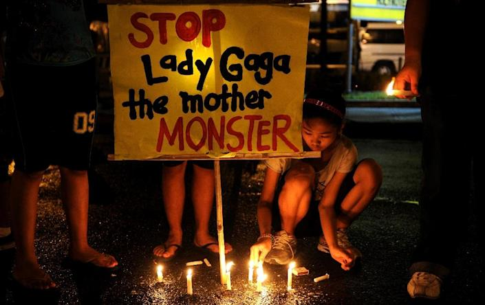A member of Biblemode Youth Philippines lights a candle during a vigil protesting against the concert of US singer Lady Gaga near the concert venue in Manila on May 21, 2012 (AFP Photo/Noel Celis)
