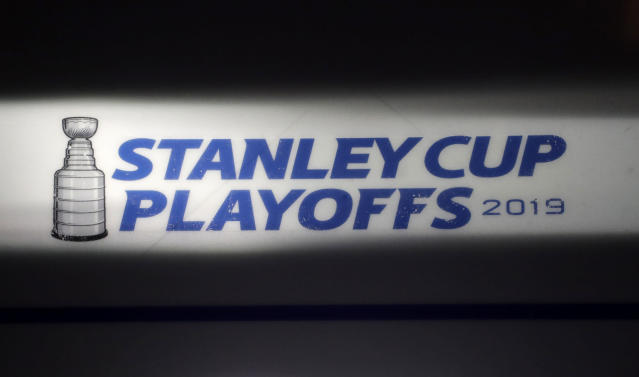 FILE - In this April 26, 2019, file photo, the Stanley Cup playoffs logo is seen on the ice during a light and sound check prior to Game 1 of an NHL hockey second-round playoff series between the New York Islanders and the Carolina Hurricanes, in New York. The NHL nailed down the final details of a playoff format if the season can resume on the same day word came out that another player has tested positive for the coronavirus.(AP Photo/Julio Cortez, File)