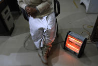 Nurse Shimray Wungreichon, 43, sits by a heater as the only nurse on overnight duty at the emergency ward of District Hospital in Ukhrul, in the northeastern Indian state of Manipur, Friday, Jan. 15, 2021. Wungreichon, who was among the first of many Indian health workers to be vaccinated on Saturday, rues about the lack of facilities in the government hospital that caters to a population of around 180,000 people, mostly indigenous Tangkhul Nagas. (AP Photo/Yirmiyan Arthur)