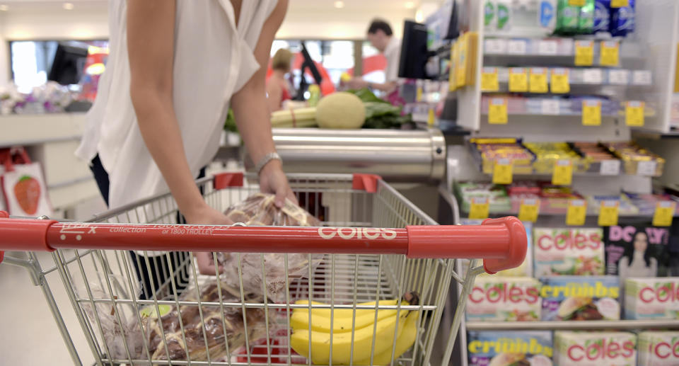 A customer transfers items from a shopping cart to a checkout counter at a Coles supermarket.