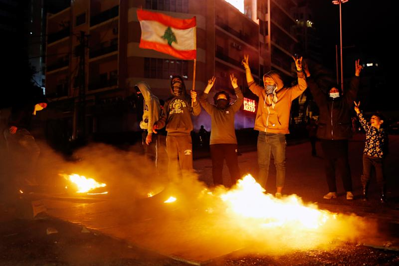 Anti-government demonstrators hold a national flag as burning tires block a road during a protest in Beirut, Lebanon, Thursday, Jan. 16, 2020. Lebanese protesters Thursday decried security forces' use of violence during rallies over the past two days, including attacks on journalists and the detention of over 100 people. (AP Photo/Bilal Hussein)