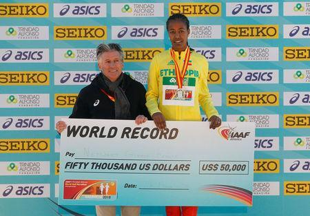 IAAF President Sebastian Coe presents Ethiopia's Netsanet Gudeta Kebede with a cheque after she won the women's race and setting a new world record. REUTERS/Heino Kalis