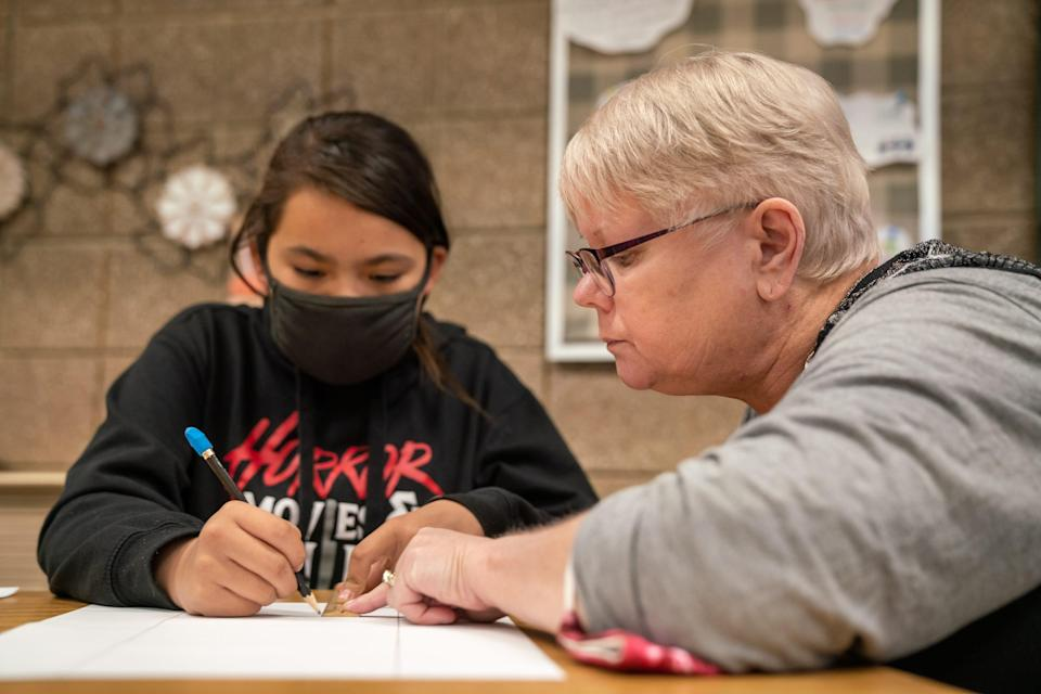 Teacher Sheryl Kohl helps line up a ruler as her student works on an art project. A 37-year veteran of the Poplar school district, Kohl said it's difficult to find and keep enough teachers to stay there.