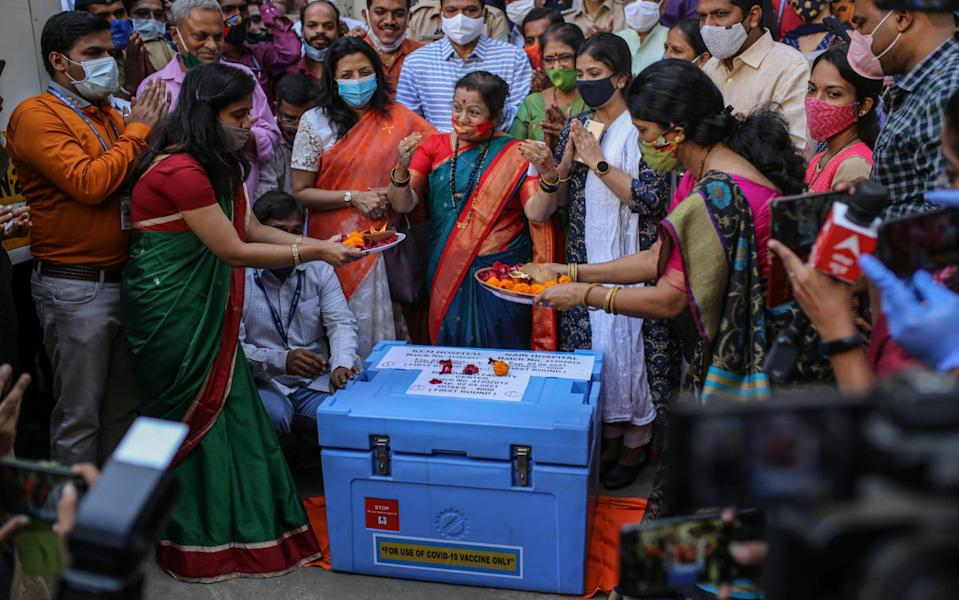 Government officials pray over a vaccine storage box containing Covid-19 vaccines due to leave for various vaccination centres in Mumbai, India, on Friday - Dhiraj Singh/Bloomberg