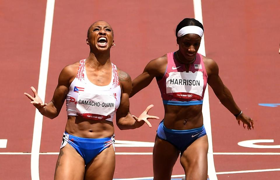 A female runner spreads her fingers and, holding her head back, shouts up at the sky.