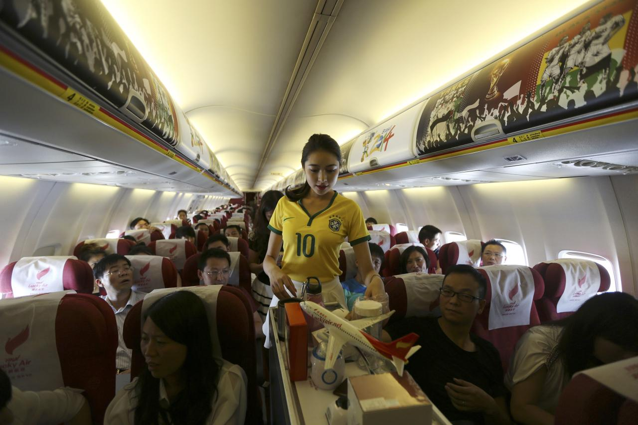 A flight attendant wearing a Brazil soccer team jersey serves passengers on an airplane travelling from Kunming to Hangzhou June 23, 2014. A Chinese airline company renovated the cabin of one of its flights then dressed the flight attendants with soccer jerseys as a way to celebrate the 2014 Brazil World Cup and hoping to attract more customers, local media reported. REUTERS/Wong Campion (CHINA - Tags: SPORT SOCCER WORLD CUP SOCIETY TRANSPORT)
