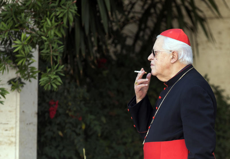 "Cardinal Jose' Policarpo smokes during a pause of the morning session of an extraordinary consistory in the Synod hall at the Vatican City, Friday, Feb. 21, 2014. Pope Francis is leading a two-day meeting urging his cardinals to find ""intelligent, courageous"" ways to help families under threat today without delving into case-by-case options to get around Catholic doctrine. He said the church must find ways to help families with pastoral care that is ""full of love.""(AP Photo/Alessandra Tarantino)"