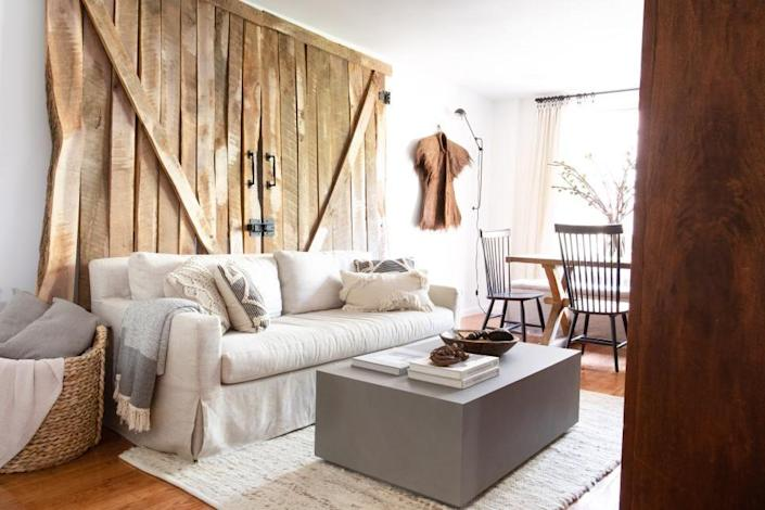 """<p>Designer and TV host <a href=""""https://www.mikelwelch.com/"""" rel=""""nofollow noopener"""" target=""""_blank"""" data-ylk=""""slk:Mikel Welch"""" class=""""link rapid-noclick-resp"""">Mikel Welch</a> repurposed old barn doors as a striking, conversation-starting accent in this quaint New York City apartment. The innovative wall decor piece grounds the space and adds a sense of warmth. </p>"""