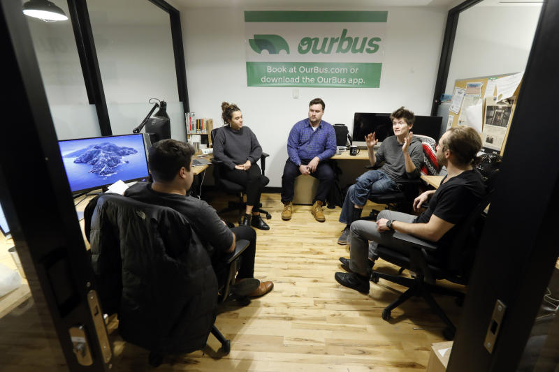 """In this Monday, Nov. 4, 2019 photo, from left to right, Steve Motino, Lea Knio, Samuel Brownsword, Axel Hellman and Anthony Giordano, of OurBus, meet in their WeWork office space, in New York. WeWork is slashing the lavish spending that fueled the office-sharing company's breakneck growth while racking up unsustainable losses that ultimately turned off Wall Street investors, forcing it to shelve its initial public offering. For now, many of its members are rooting for the company, including Hellman. """"It's easy to poke fun at the motivational signage and fruit water,"""" Hellman said. """"But in reality, it's the network available to us through WeWork and the flexibility they offer that makes the company valuable to us.""""  (AP Photo/Richard Drew)"""