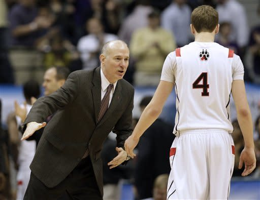 Northeastern head coach Bill Coen greets Northeastern guard David Walker (4) during the first half of the CAA Conference tournament championship NCAA college basketball game against James Madison in Richmond, Va., Monday, March 11, 2013. (AP Photo/Steve Helber)