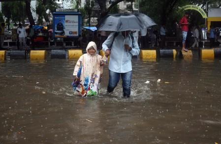 A man and his daughter wade through a waterlogged street during heavy rains in Mumbai