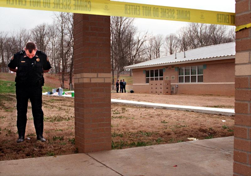 A police officer stands at the perimeter of the crime scene