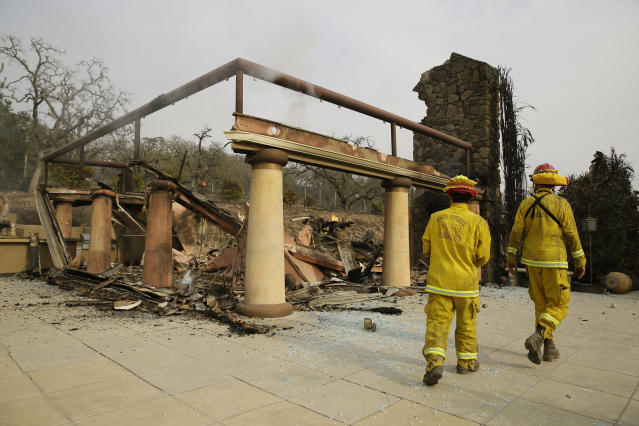 <p>A pair of Napa County firemen walk through the remains of the Signorello Estate Winery Tuesday, Oct. 10, 2017, in Napa, Calif. Worried California vintners surveyed the damage to their vineyards and wineries Tuesday after wildfires swept through several counties whose famous names have become synonymous with fine food and drink. (Photo: Eric Risberg/AP) </p>