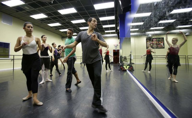 In this photo taken Friday, May 17, 2013, ballet master Eriberto Jimenez, right, gives instructions during practice in a dance studio in Miami. These dancers could be among the young talent of any ballet company, but for the moment they are something else: Immigrants in the United States trying to land dancing opportunities while navigating cultural differences and learning English. The ballerinas fled from the Cuban National Ballet while on tour in Mexico in April, and crossed the border into Texas. (AP Photo/Alan Diaz)