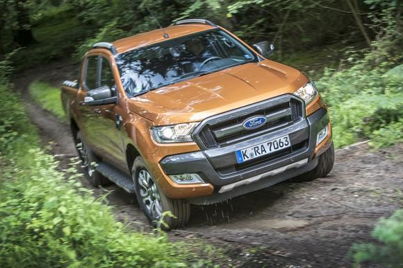 An orange Ford Ranger pickup with European license plates driving on a muddy trail.