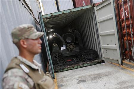 A police officer stands guard at a container holding arms seized from a North Korean flagged ship in Colon City