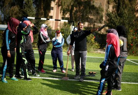 Palestinian baseball coach Mahmoud Tafesh gestures as he trains women in Khan Younis in the southern Gaza Strip March 19, 2017.  REUTERS/Mohammed Salem
